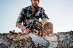 Yrkesmässig stark lumberman som sågar en stor utslagsplats på sågverket royaltyfria bilder