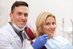 Yrkesmässig tandläkare som arbetar på hans tand- klinik royaltyfria bilder