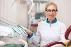 Yrkesmässig tandläkare som arbetar på hans tand- klinik royaltyfria foton