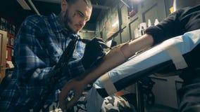 Yrkesmässig tattooerteckning på en handprotes, handikappad person stock video