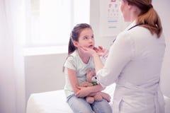 Yrkesmässig undersökande flicka för familjläkare som har den öm halsen royaltyfri fotografi