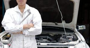 Yrkesmässig ung asiatisk mekanikerman i enhetlig innehavskiftnyckel mot bilen i öppen huv på reparationsgaraget royaltyfria foton