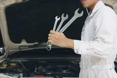 Yrkesmässig ung asiatisk mekanikerman i enhetlig innehavskiftnyckel mot bilen i öppen huv på reparationsgaraget arkivbild