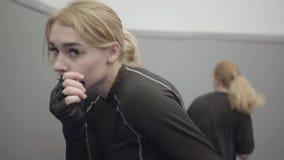 Yrkesmässig ung härlig blond kvinnaboxning i kameran i svarta boxas handskar arkivfilmer
