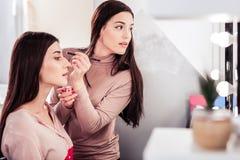 Yrkesmässig ung makeupkonstnär som gör ögonbrynen arkivfoto