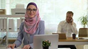Yrkesmässig ung muslim affärskvinna som ser att skratta för kamera stock video