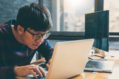 Yrkesmässig utvecklingsprogrammerare som arbetar, i att programmera websiten en programvara och att kodifiera teknologi och att s arkivfoto