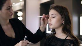 Yrkesmässig visagist - brunettkvinna med perfekt röd manikyr genom att använda makeupborsten för att applicera ögonskuggor på ögo lager videofilmer