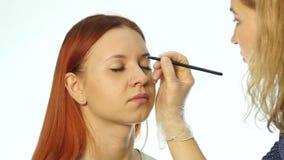 Yrkesmässiga ögonbryn för teckning för sminkkonstnär av den härliga klienten Skönhet och modebegrepp arkivfilmer