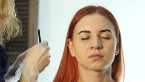 Yrkesmässiga ögonbryn för teckning för sminkkonstnär av den härliga klienten Skönhet och modebegrepp stock video