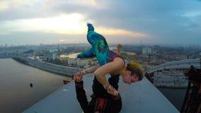 Yrkesmässiga akrobater som överst gör farliga jippon av bron, extrem hobby stock video