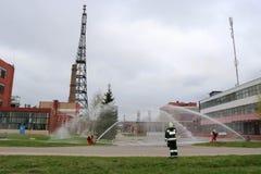 Yrkesmässiga brandmän i orange fireresistant dräkter i vita hjälmar med gasmaskar testar brandslangar och brandvapen till e fotografering för bildbyråer