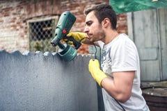 Yrkesmässiga byggnadsarbetaremålningväggar på husrenovering Royaltyfri Bild