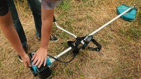 Yrkesmässiga gräsklipparestarter gasar gräsmattabeskäraren och starter för att arbeta stock video