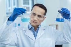 Yrkesmässiga hållande medicinska flaskor för labbarbetare Arkivfoto