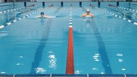 Yrkesmässiga idrottsman nensimmare som konkurrerar i simbassäng lager videofilmer