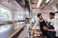 Yrkesmässiga kockar som arbetar i restaurangkök royaltyfri foto