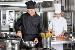 Yrkesmässiga kockar som förbereder spagetti Royaltyfri Fotografi