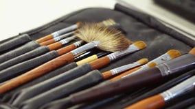 Yrkesmässiga makeupborstar ligger i ett fall på en tabell, kameraflyttningar lager videofilmer