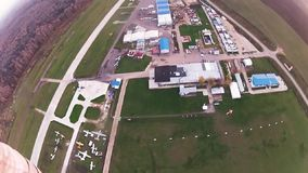 Yrkesmässiga skydivers flyger i ovannämnt grönt fält för himmel landning extremt parachute arkivfilmer
