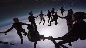 Yrkesmässiga skydivers gör bildande i himmel extremt gå för litet barn för solnedgång för holding för hand för trädgård för barn  arkivfilmer
