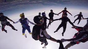Yrkesmässiga skydivers gör bildande i molnig himmel extrem sport gå för litet barn för solnedgång för holding för hand för trädgå stock video