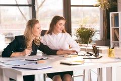 Yrkesmässiga unga affärskvinnor som sitter på tabellen och använder bärbara datorn Royaltyfri Fotografi