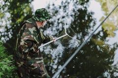 Yrkesmässigt äldre använda för sportfiskare som är netto för att fiska royaltyfri bild