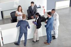 Yrkesmässigt affärsfolk som kontrollerar på mottagandet arkivfoto