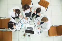 yrkesmässigt affärslag som framkallar en ny finansiell strategi av företaget på ett arbetsläge i ett modernt kontor royaltyfri bild