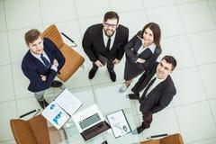 Yrkesmässigt affärslag som ser stående det upp near skrivbordet Royaltyfria Bilder