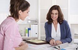 Yrkesmässigt affärsmöte under kvinna två: klienten och råder Fotografering för Bildbyråer