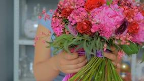 Yrkesmässigt blomsterhandlareinnehav och visningbukett på studion lager videofilmer