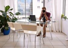 Yrkesmässigt fotografsammanträde i hans hem- studio Royaltyfri Fotografi
