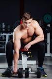 Yrkesmässigt kroppsbyggaresammanträde på bänken som vilar mellan övningar med hantlar på idrottshallen bifokal royaltyfri fotografi