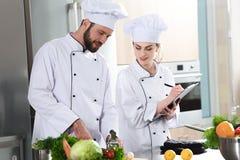 Yrkesmässigt lag av kockar som kontrollerar recept under royaltyfria bilder