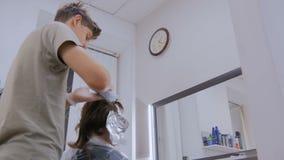 Yrkesmässigt manligt frisörfärgläggninghår av kvinnaklienten på studion arkivfilmer