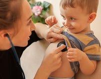 Yrkesmässigt pediatriskt undersöka för selektiv fokus till lite pojken Manipulera genom att använda en stetoskop för att lyssna t Arkivbild