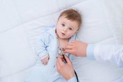Yrkesmässigt pediatriskt undersökande spädbarn royaltyfri bild