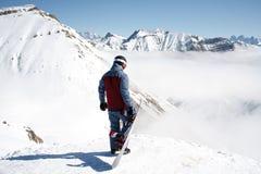 Yrkesmässigt snowboarderanseende med snowboarden i bergen Härligt berglandskap i bakgrunden Fotografering för Bildbyråer