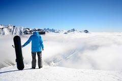 Yrkesmässigt snowboarderanseende med snowboarden i bergen Härligt berglandskap i bakgrunden Arkivfoto