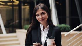 Yrkesmässigt ungt affärskvinnaanseende på den stads- gatan genom att använda smartphone- och drinkkaffe Henne som ser in i kamera stock video