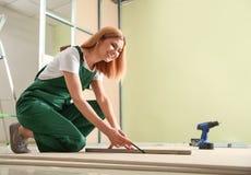 Yrkesm?ssig byggm?stare som arbetar med drywallen Hem- reparationsservice arkivbilder