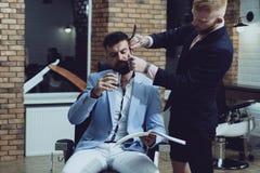 Yrkesm?ssig fris?r i frisersalonginre Manlig klient som f?r frisyr av fris?ren Balsam p? torra kroppsdelar till royaltyfri bild