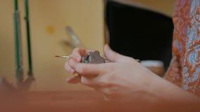 Yrkesm?ssig keramiker som m?lar den keramiska souvenirencentmyntvisslingen i krukmakeriseminarium stock video