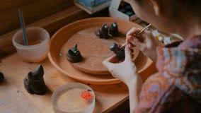 Yrkesm?ssig keramiker som m?lar den keramiska souvenirencentmyntvisslingen i krukmakeriseminarium lager videofilmer