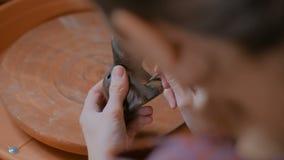 Yrkesm?ssig keramiker som m?lar den keramiska souvenirencentmyntvisslingen i krukmakeriseminarium arkivfilmer