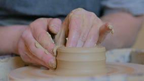 Yrkesm?ssig manlig keramiker som arbetar med lera p? hjulet f?r keramiker` s lager videofilmer