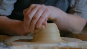 Yrkesm?ssig manlig keramiker som arbetar med lera p? hjulet f?r keramiker` s arkivfilmer