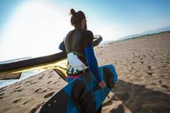 Yrkesm?ssigt surfareanseende f?r Caucasian man p? den sandiga stranden med hans drake och br?de royaltyfri bild
